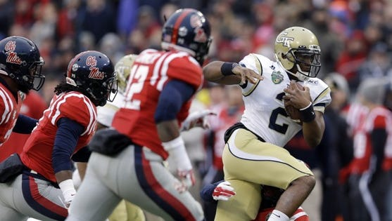 Georgia Tech quarterback Vad Lee (2) tries to scramble away from a group of Mississippi defenders in the first quarter of the NCAA college football Music City Bowl game on Monday, Dec. 30, 2013, in Nashville, Tenn. (AP Photo/Mark Humphrey)