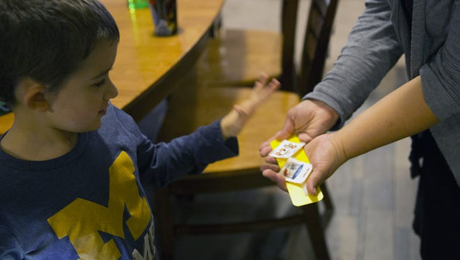 Micah Wade uses a book with laminated pictures to communicate with his mom, Jessica Wade, at home in Kalamazoo, Mich. Almost 8, Micah doesn't speak.