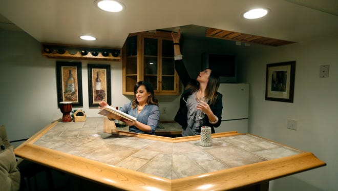 Chelse Moffatt and Susan Glenz of Keller Williams Realty arrange the bar area to prepare a home for sale in Churchville.