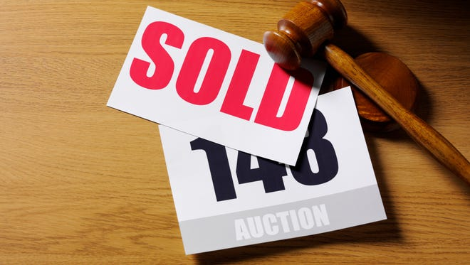 Red sold sign and auction paddle.