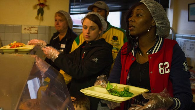 From left, Julie Franklin, Melissa Younglove and Maika Jones serve pizza at Haven of Rest Friday night.