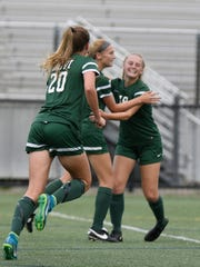 Novi's Avery Fenchel is congratulated after scoring the first goal by Julia Stadtherr (20) and Laine Fenchel (left). Novi beat Troy in the Div. 1 semifinal game 4-1 to advance to Friday's championship game against Grand Blanc.