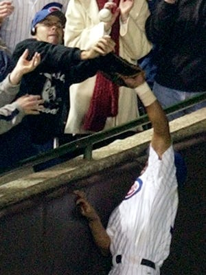Chicago Cubs' Moises Alou tries to catch a foul ball as Steve Bartman reach as well during the 2003 National League Championship Series.