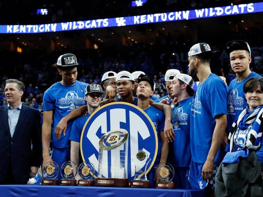 Kentucky head coach John Calipari, left, and his players accept their trophies after beating Tennessee in an NCAA college basketball championship game at the Southeastern Conference tournament Sunday, March 11, 2018, in St. Louis. Kentucky won 77-72. (AP Photo/Jeff Roberson)