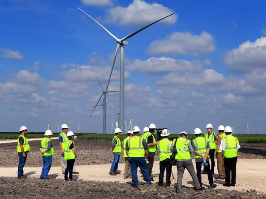 Contractors observe wind turbines during a tour of the wind farm located off Farm-to-Market Road 70 near Chapman Ranch on Tuesday, Aug. 1, 2017.