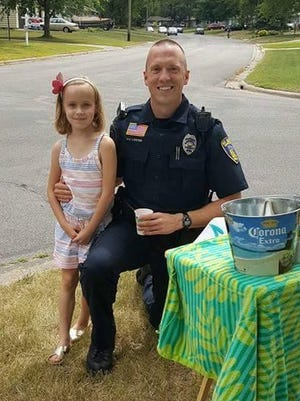 Officer Jeff Lester made a stop by Presley Anhorn's lemonade stand Monday, July 4, 2016. Lester was one of four officers who stopped by the stand Monday afternoon.