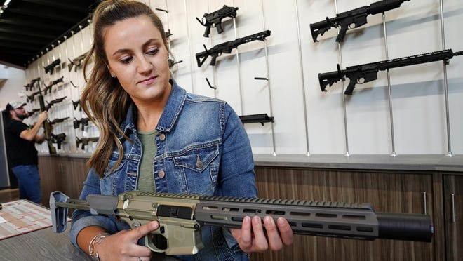 Brenna McCoubrey, marketing manager at White Birch Armory in Dover, holds a Q Honey badger .300 Blackout sporting rifle. The veteran-owned business specializes in firearms training and sales.