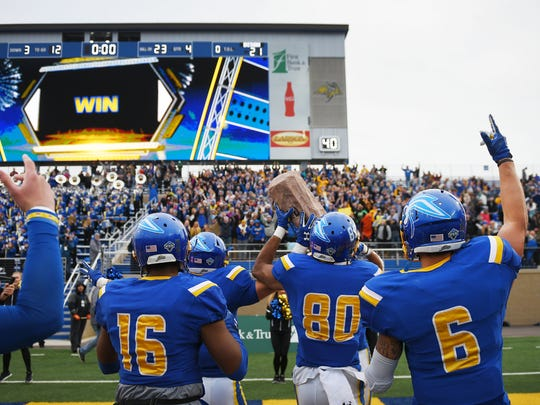 South Dakota State University's Brandon Thomas (16) Adam Anderson (80) and Makiah Slade (6) take the Dakota Marker along with their team over to the student section after their win over North Dakota State University Saturday, Nov. 4, at Dana Dykhouse Stadium in Brookings.