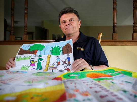 John Koehler holds and is surrounded by drawings done by 7th and 8th grade students depicting unexploded ordinance from Quang Tri Province in Vietnam Wednesday, May 11, 2016 in Appleton, Wis. Koehler, who served in the Vietnam War, took a trip back to Vietnam where he received these drawings from the Project Renew museum.Danny Damiani/USA TODAY NETWORK-Wisconsin