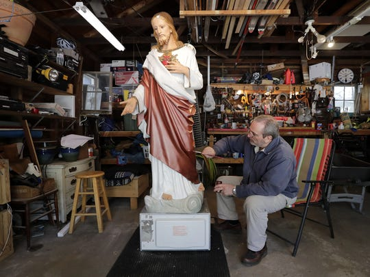 Bruce Nufer, a retired art teacher, paints a near life-size plaster statue of Jesus on Tuesday at his home in Menasha. It will take about 30 hours of work for Nufer to plaster and paint the statue that was located in St. Patrick's School. It will be returned to St. Patrick's Parish in Menasha.