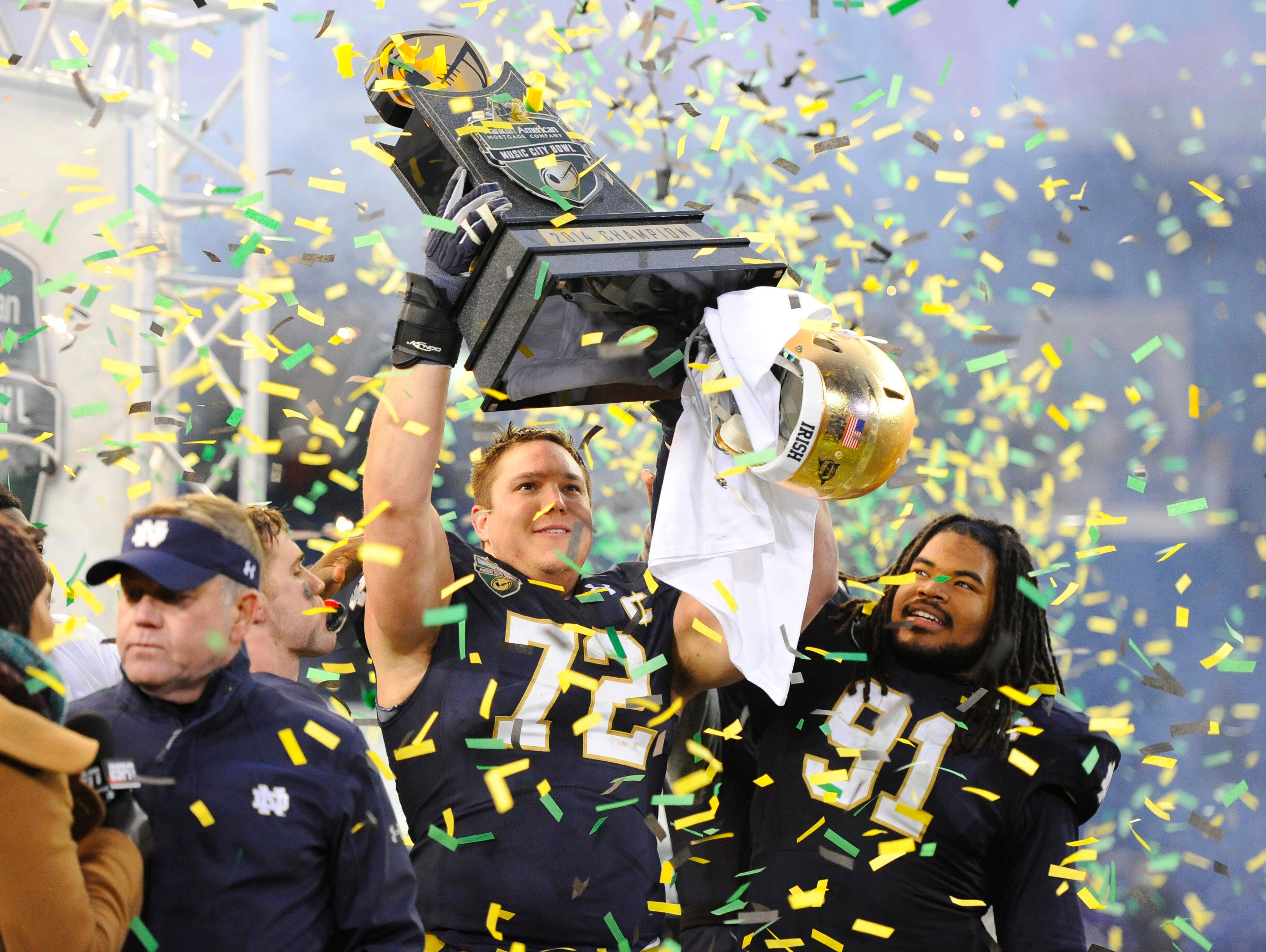 Notre Dame offensive lineman Nick Martin (72) and defensive lineman Sheldon Day (91) celebrate after winning the Music City Bowl.