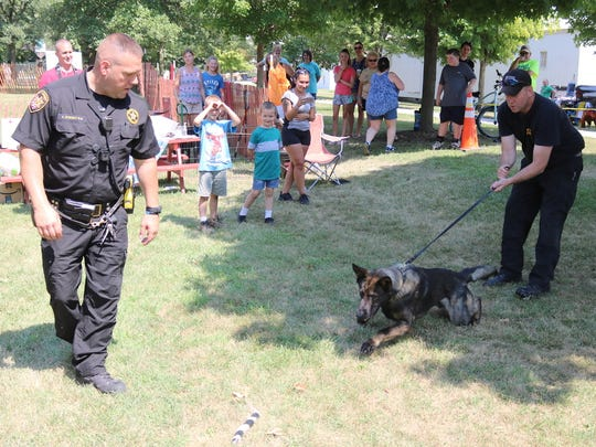 """Deputy Allen Dorsey and Deputy George Dorsey, of the Sandusky County Sheriff's Office, works with K-9 Hayes during a demonstration at """"Woof-Fest"""" in Lindsey on Saturday."""