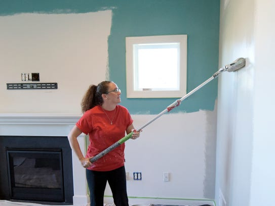 Painting by Tanya employee Melissa Mace paints a wall
