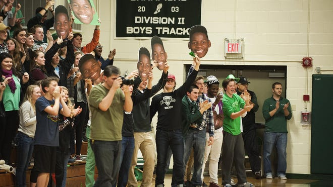 Rice fans cheer for Ben Shungu (11) (not pictured) who made his 1000th point during the boys basketball game between the Essex Hornets and the Rice Green Knights at Rice Memorial High School on Tuesday night in South Burlington.