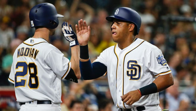 San Diego Padres' Yangervis Solarte, right, is congratulated by Nick Noonan after scoring against the Arizona Diamondbacks in the third first inning of a baseball game Thursday, Aug. 18, 2016, in San Diego.