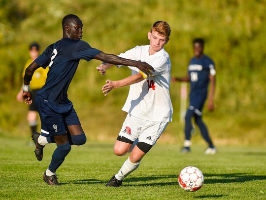 Champlain Valley Union's Nate Coffin, right, tries to get past Burlington's Rida Kora in Hinesburg on Monday, September 18, 2017.