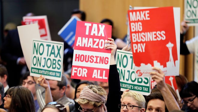 """Protesters crowd the meeting at which the Seattle City Council repealed the so-called """"head tax"""" targeting the city's largest employers."""
