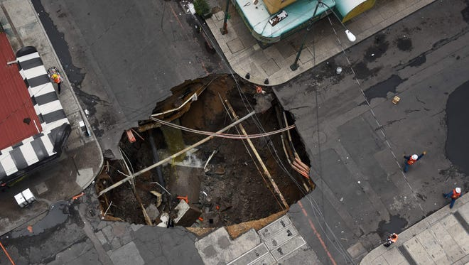 Civil protection personnel work around the seven meters deep and ten in diameter hole caused after heavy rains unleashed during the passage of Tropical Storm Lidia in the Mexican Pacific, in Mexico City, on Aug. 31, 2017.