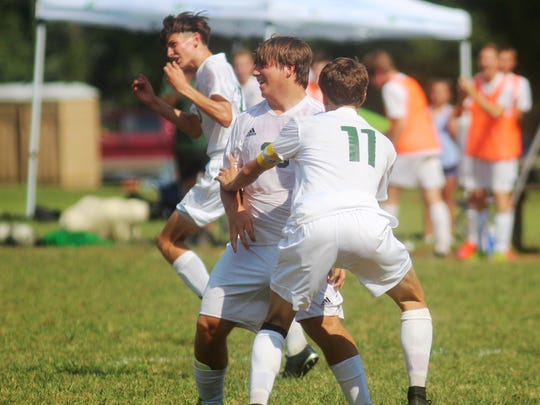 Brossart soccer players celebrate a goal by senior Cody Chism, No. 11, on Sept. 10.