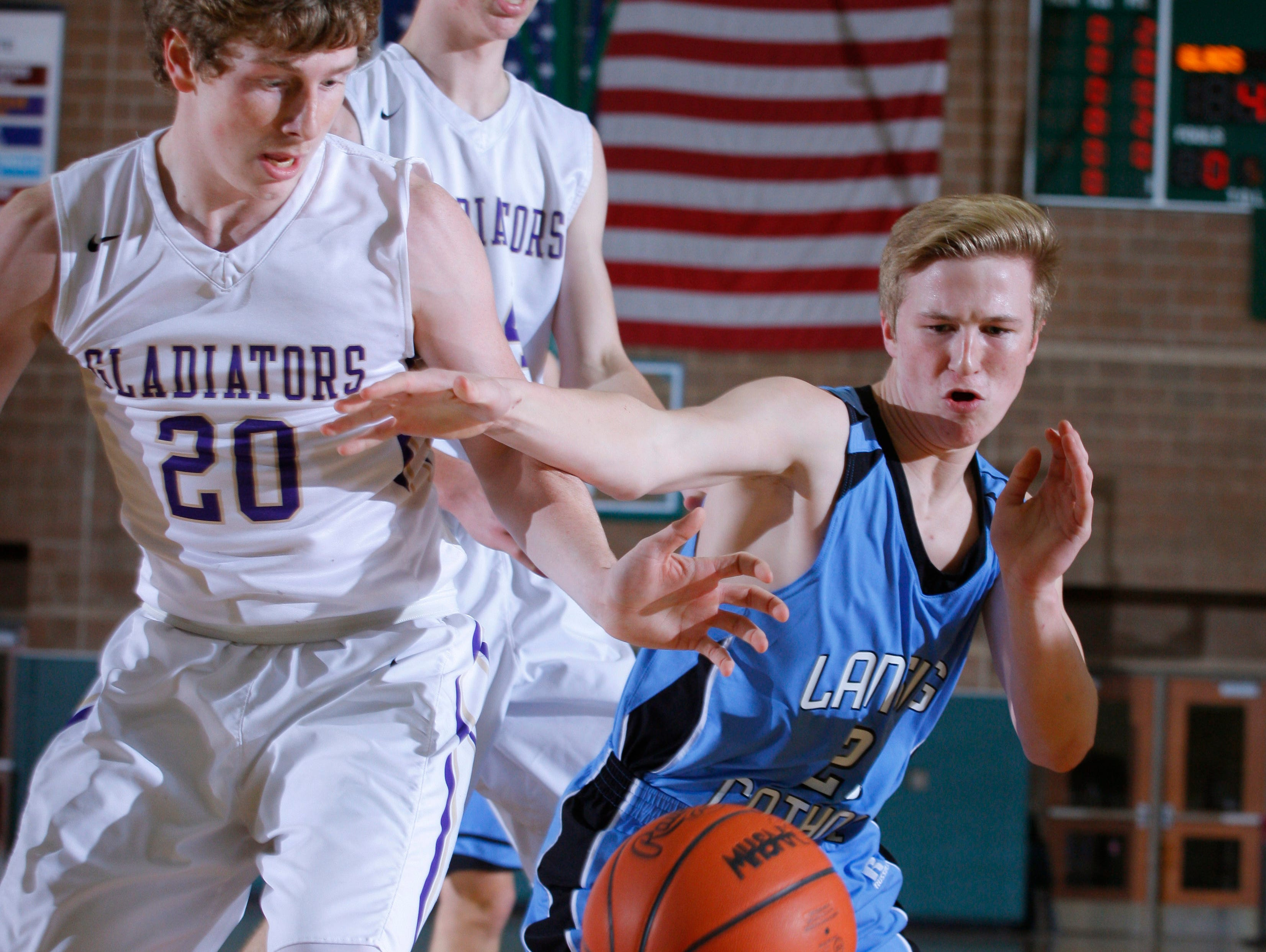 Fowlerville's Cam Brigham, left, and Lansing Catholic's Matthew Plaehn vie for the ball during their district game Monday, March 6, 2017, in East Lansing, Mich. Fowlerville won 66-52.