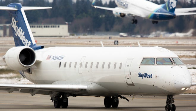 A SkyWest Bombardier CRJ taxies for departure as an Alaska Airlines Boeing 737 takes off from Seattle-Tacoma International Airport in January 2017.