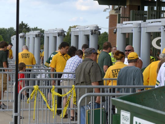 Fans make their way through metal detectors as they