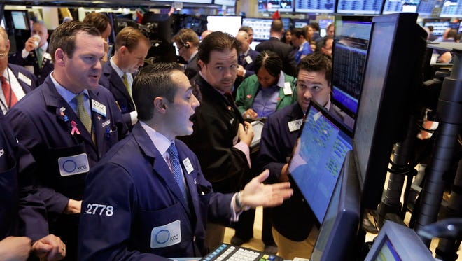 Specialist Michael Gagliano, foreground center, works with traders at his post on the floor of the New York Stock Exchange, on Wednesday.