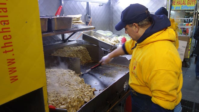 A griddle man preps chicken for one of The Halal Guys' carts in Manhattan.