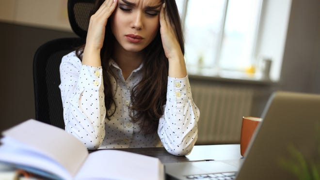 Woman holding head looking stressed with books and laptop