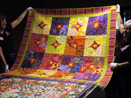 Susan Bellamy, left, and Judie Fleming, right, hold up a quilt to be judged at the 2012 Best of the Valley Quilt Show at the McDermont Field House in Lindsay. Almost 250 quilts were judged that day.