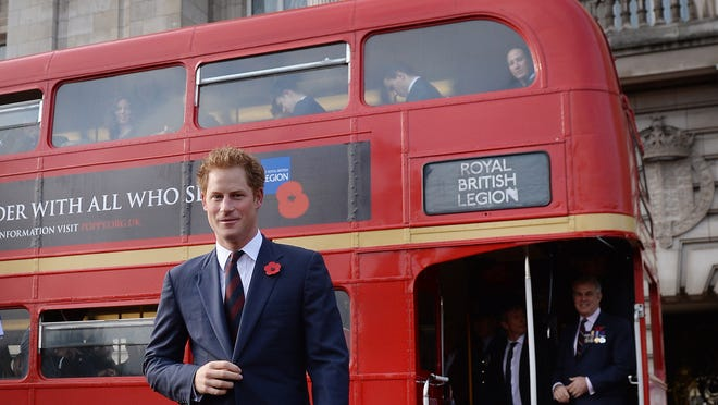Prince Harry meets the poppy bus collecting for Poppy Day appeal at Buckingham Palace on Oct. 30.