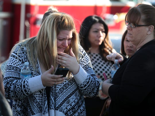 A woman cries at the scene of an active shooting on S. Waterman Avenue in San Bernardino, Calif.