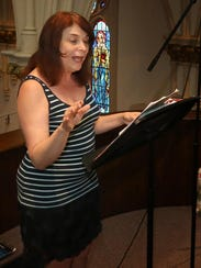 Arlene Siconolfi directs a 10-member choir Monday during