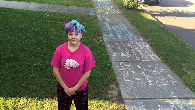 Chelsea Pike, 14, covered the sidewalk of an entire city block in Rochester's Corn Hill neighborhood with biblical verses and uplifting messages.