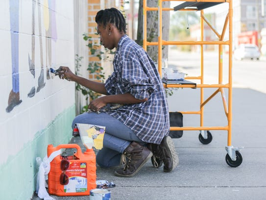 Ajia Coleman Durham works to finish a mural project