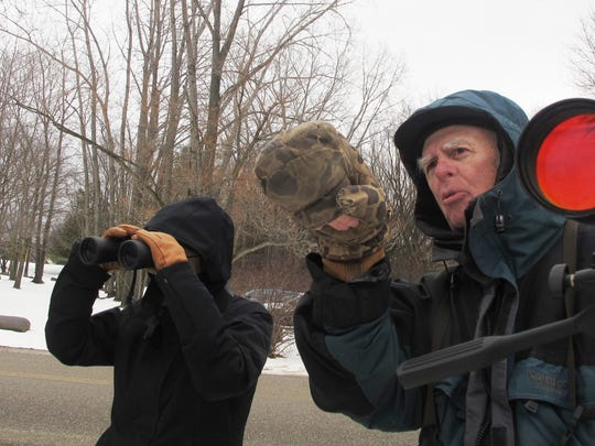 Bruce MacPherson, a veteran birder from South Burlington, points out waterfowl to Sidney Eley of Burlington on Saturday along Lake Champlain. The two were among dozens of volunteers taking a survey of bald eagles.