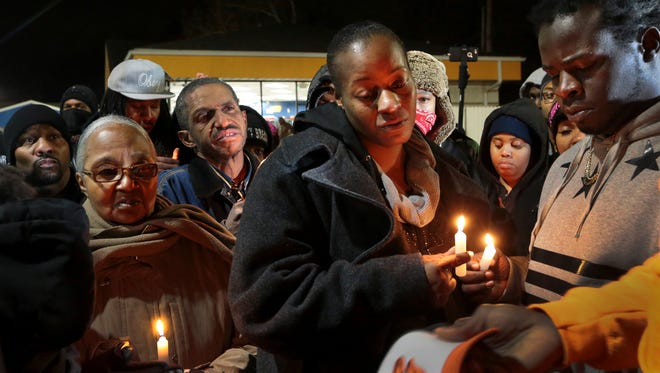 Toni Martin-Green (front center) and her husband Jerome Green, right, participate in a candlelight vigil at a Berkeley, Mo., gas station on Wednesday, Dec. 24, 2014.