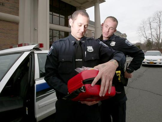 Clarkstown Police Officers Matthew Bender and Will Cunnane look at a Narcan kit at police headquarters April 4 in New City. The nasal spray atomizer will be kept with the medical kit and defibrillator in patrol cars.