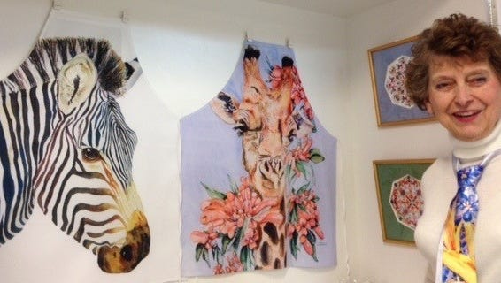Julie Dawson shows some of her Pop Up store items available from March 17th until April  2nd    at the store at 135 N. Woodward. Two aprons with her paintings transferred to fabric and two of her kaleidoscope designs will be available along with 60 other interesting products.