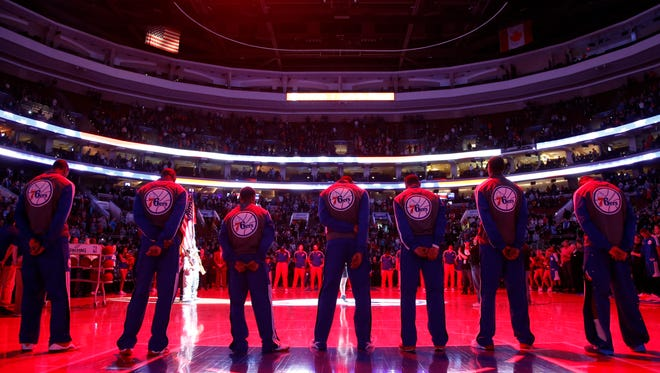 Philadelphia 76ers stand during the playing of the national anthem before an NBA basketball game against the Detroit Pistons, Saturday, March 29, 2014, in Philadelphia. (AP Photo/Matt Slocum)