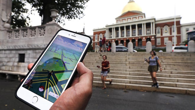 """A """"Pokemon Go"""" player walks through the Boston Common, outside the Massachusetts Statehouse in Boston. Many markers and historical sites are Pokestops, creating the possibility that players will be exposed to some history in between catching monsters."""