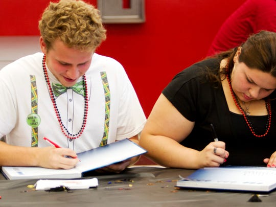South Fort Myers High School students, Yatniel Ramos,18, and Jesika Torres,17, sign yearbooks during senior breakfast on Friday 5/16/2014.  This year students can also download an app that features videos and other features from the school year.