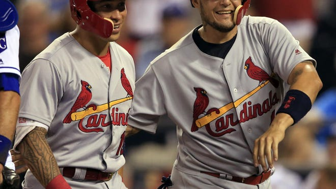 St. Louis Cardinals' Kolten Wong, left, and teammate Yadier Molina, right, celebrate after Wong's two-run home run during the eighth inning of a baseball game at Kauffman Stadium in Kansas City, Mo., Monday, Aug. 7, 2017.