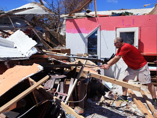 Lance Esswein digs through the rubble of his wife's