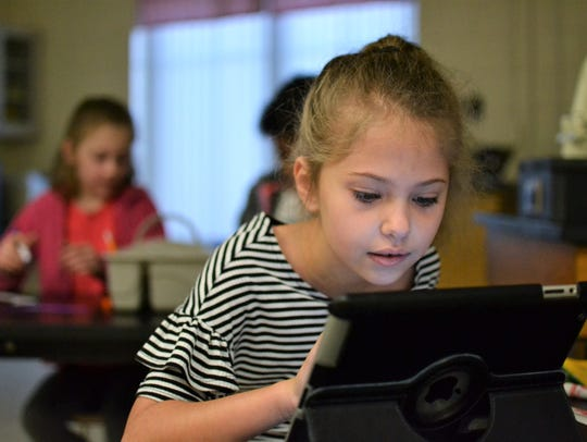 Catherine Jaskwhich, 8, works on an iPad during Sandy