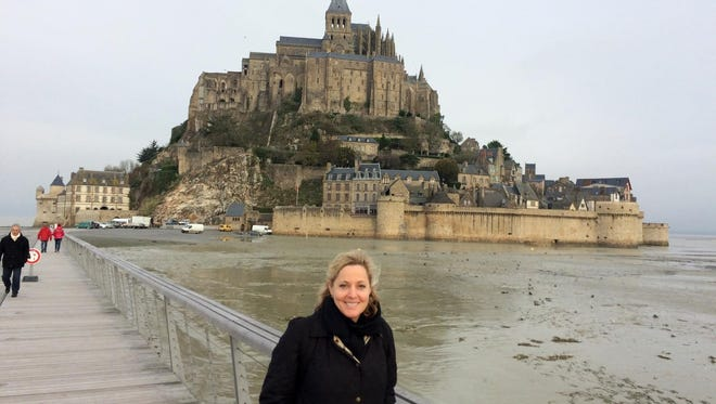In this Nov. 27 photo, Laura Grimmer poses in front of the Mont Saint-Michel monastery in Normandy, France. Grimmer and her husband have spent eight of the last 10 Thanksgiving holidays in France. They did not consider changing their plans despite the recent terror attacks in Paris.