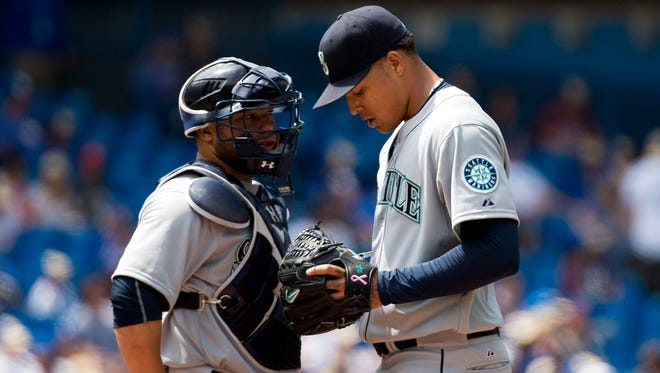 Seattle Mariners starting pitcher Taijuan Walker, right, talks with catcher Welington Castillo, left, after allowing four runs during fifth-inning baseball game action against the Toronto Blue Jays in Toronto, Sunday, May 24, 2015.