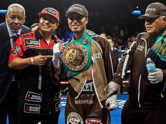 Mikey Garcia, center, smiles and poses for photos after defeating Adrien Broner during a boxing bout Saturday, July 29, 2017, in New York. (AP Photo/Andres Kudacki)
