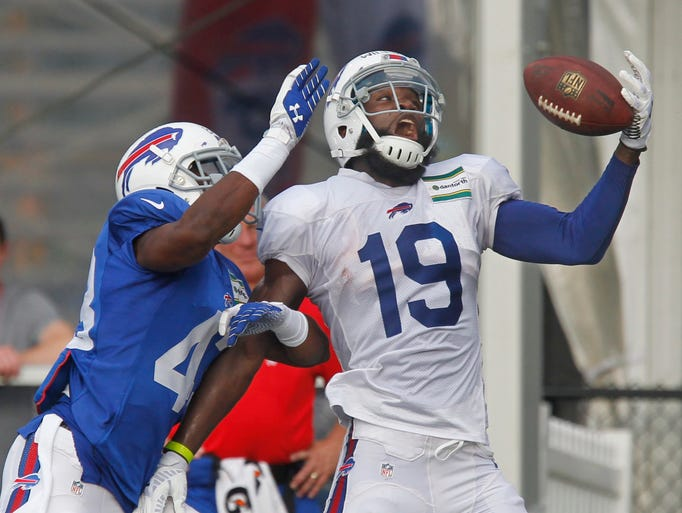 Buffalo wide receiver Mike Williams can't hold onto a one handed catch as safety Derek Brim, left, knocks the ball away during the Bills training camp session Saturday night, July 26, 2014 at St. John Fisher College in Pittsford.