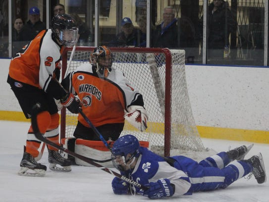 A Catholic Central player slides by Brother Rice goalie